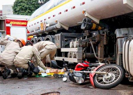 Motociclista para sob carreta e roda passa por cima de perna