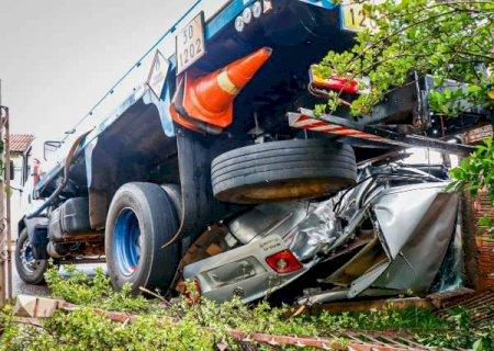 """Caminhão carregado com combustível perde o freio, prensa carro e """"sobe"""" em muro"""